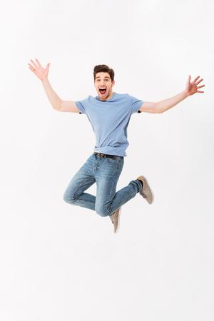 Photo pleine longueur d'un homme drôle des années 30 en t-shirt décontracté et jeans sautant avec les bras en levant isolé sur fond blanc