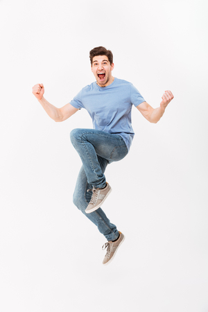 Full-length photo of excited man 30s in casual t-shirt and jeans levitating while expressing triumph with clenching fists isolated over white background