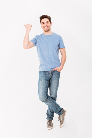 Full-length image of handsome man rejoicing and pointing finger aside on copyspace isolated over white background