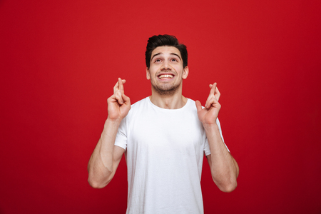 Portrait of a smiling young man in white t-shirt holding fingers crossed for good luck isolated over red background