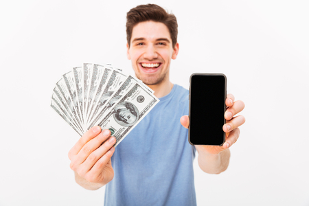 Excited man in casual t-shirt demonstrating his money prize and copyspace screen of smartphone isolated over white wall