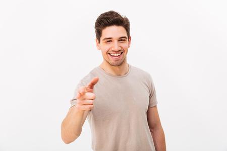 Hombre alegre confidente con cabello castaño gesticulando con el dedo índice en la cámara, lo que significa oye, aislado sobre fondo blanco.