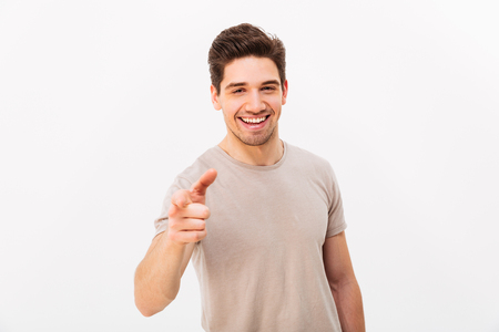 Confident cheerful man with brown hair gesturing index finger on camera meaning hey you isolated over white background Foto de archivo