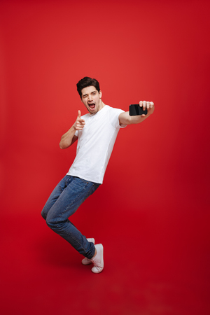 Full length portrait of a handsome young man in white t-shirt pointing finger while taking a selfie and posing isolated over red background
