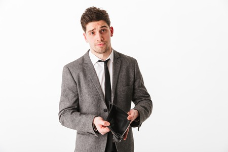 Portrait of a sad young businessman showing empty wallet isolated over white background Stock Photo