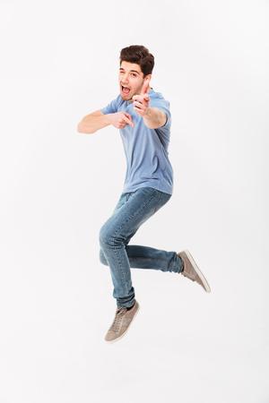 Foto integrale dell'uomo bello 30s in maglietta e jeans casuali divertendosi e indicando i dito indice sulla macchina fotografica isolata sopra fondo bianco Archivio Fotografico
