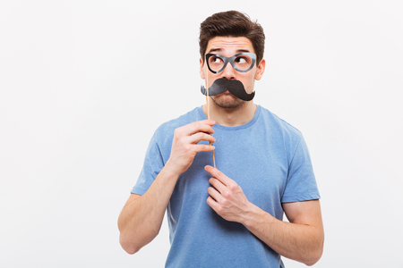 Image of Pensive man in fake mustache and eyeglasses looking away over grey background Reklamní fotografie