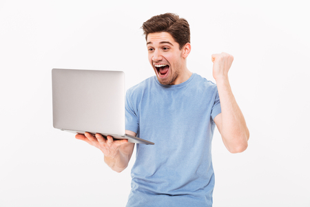 Happy successful man in t-shirt clenching fist like lucky guy or winner while working in internet on laptop isolated over white background