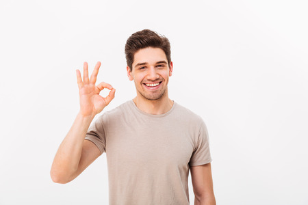 Optimistic man having bristle and brown hair showing ok sign on camera with sincere look isolated over white background 写真素材 - 97778253