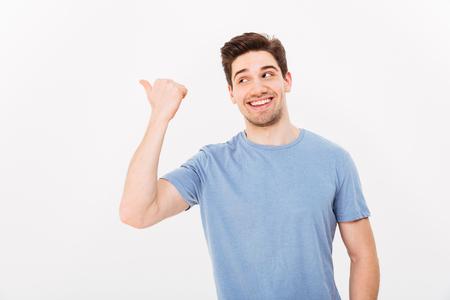 コピースペースのテキストや白い背景に隔離された製品に指を向けるカジュアルな服で輝く笑顔を持つ男のクローズアップ画像 写真素材