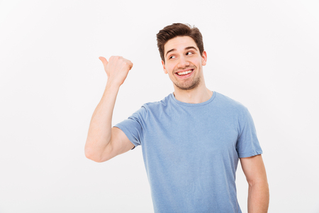 Closeup image of man with shining smile in casual clothing pointing finger aside on copyspace text or product isolated over white background