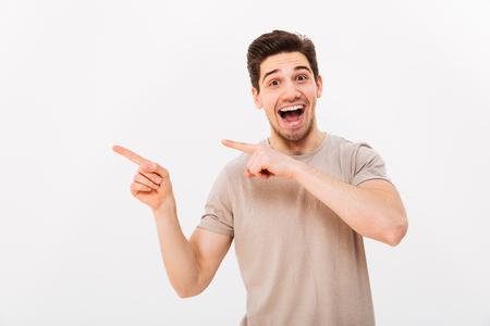 カジュアルなTシャツを着た興奮した男は、コピースペースのテキストや白い背景に隔離された製品に指を脇に向けて喜び、指を向ける