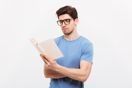 Portrait of young smart man in blue shirt wearing eyeglasses reading book with concentration isolated over white background Stok Fotoğraf - 97778327