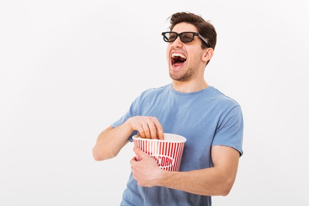 Laughing man in t-shirt and 3d glasses eating popcorn from bucket and looking away over grey background