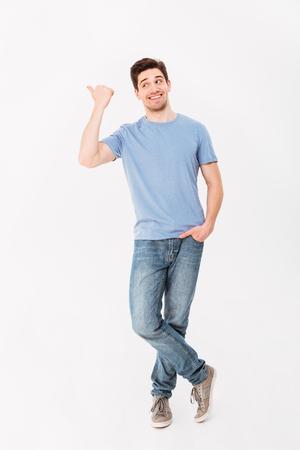 Bild in voller Länge des Mannes in der guten Laune, die Text oder Produkt mit dem Zeigen des Fingers beiseite auf dem copyspace lokalisiert über weißem Hintergrund darstellt Standard-Bild