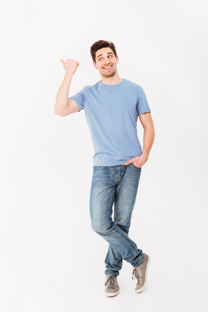 Full-length image of man in good mood presenting text or product with pointing finger aside on copyspace isolated over white background