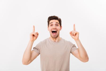 カジュアルなTシャツを着た楽観的な男性が、コピースペースのテキストや白い背景に隔離された製品に向かって、笑顔で指を上向きに見るイメージ 写真素材