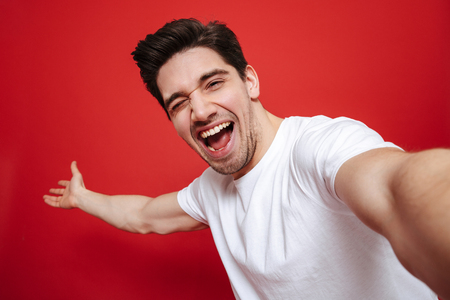 Portrait of an excited young man in white t-shirt showing peace gesture while taking a selfie isolated over red background Stockfoto
