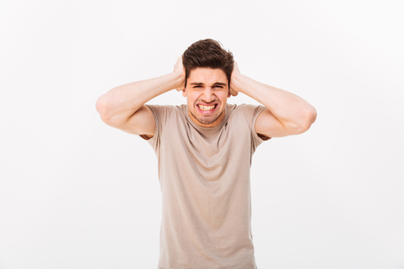 Photo of distressed emotional man 30s grabbing his head or covering ears in annoyance isolated over white background