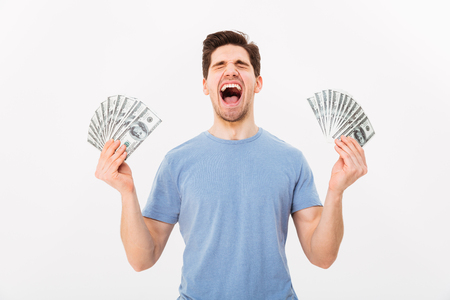 Photo of happy winner man in casual t-shirt holding two fans of money dollar banknotes isolated over white wall Stock Photo