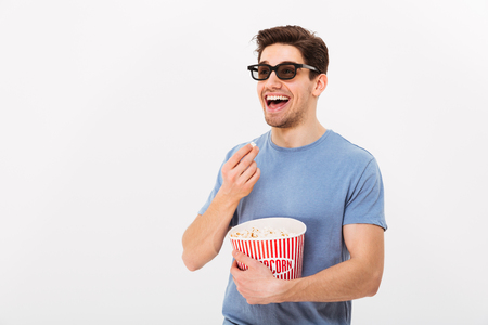 Happy man in t-shirt and 3d glasses eating popcorn from bucket and looking away over grey background Stock Photo