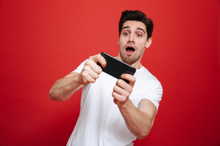 Portrait of a casual young man in white t-shirt playing games on mobile phone isolated over red background Stockfoto