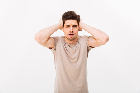 Photo of muscular adult man 30s grabbing his head or covering ears in confusion isolated over white background