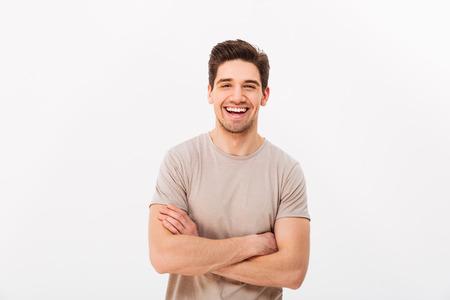 Image d'homme souriant heureux des années 30 avec des poils posant sur l'appareil photo avec les mains croisées isolé sur fond blanc
