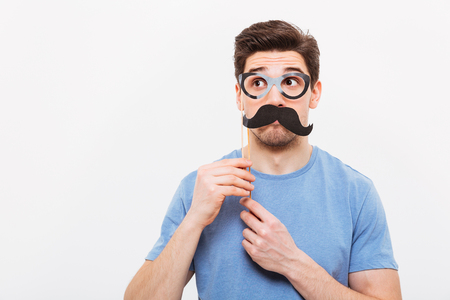 Image of Mystery man in fake mustache and eyeglasses looking away over grey background