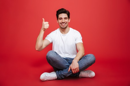 Portrait of a happy young man in white t-shirt sitting on a floor and showing thumbs up gesture isolated over red background