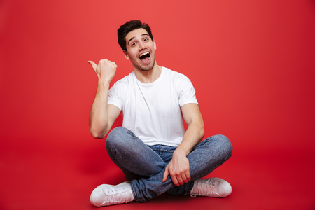 Portrait of a joyful young man in white t-shirt sitting on a floor and pointing finger away isolated over red background