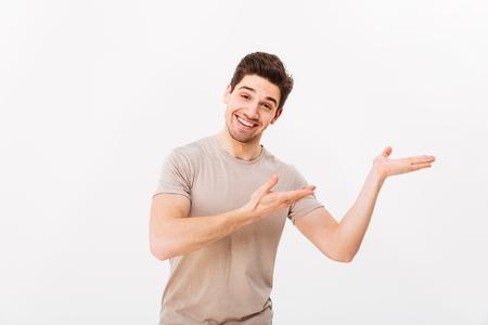 Guy gai dans la publicité de t-shirt décontracté et présentant le texte ou le produit copyspace sur la paume avec un large sourire isolé sur fond blanc