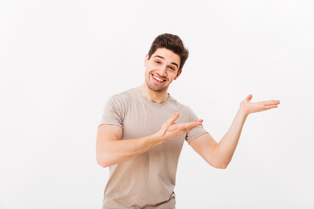Cheerful guy in casual t-shirt advertising and presenting copyspace text or product on palm with broad smile isolated over white background