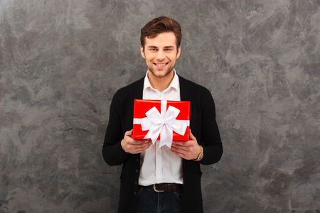 Portrait of a smiling young man dressed in shirt and jacket holding gift box isolated over gray background