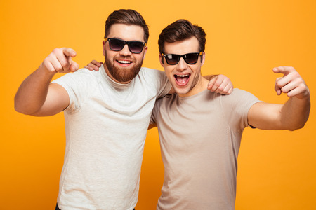 Two happy men in casual t-shirts and sunglasses hugging and pointing fingers on camera meaning hey you isolated over yellow background Reklamní fotografie