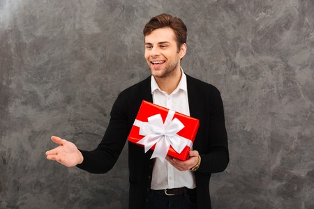 Portrait of an attractive young man dressed in shirt and jacket holding gift box and gesturing isolated over gray background