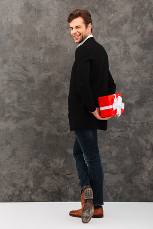 Full length portrait of a smiling young man dressed in shirt and jacket holding gift box behind his back and winking over gray background Stock Photo