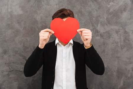 Image of young businessman standing over grey wall background. Covering face holding heart.