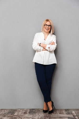 Full length image of Smiling middle-aged blonde woman in elegant clothes and eyeglasses posing with crossed arms and looking at the camera over grey background