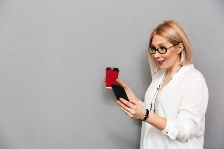Side view of surprised middle-aged blonde woman in shirt and eyeglasses using smartphone while holding cup of coffee over grey background Stock Photo