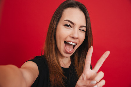Cute woman 20s in black t-shirt having fun and taking selfie with gesturing peace sign isolated over red background