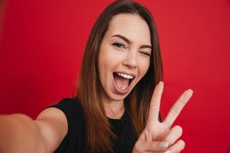 Linda mujer de 20 años en camiseta negra divirtiéndose y tomando selfie con gesticular signo de paz aislado sobre fondo rojo.