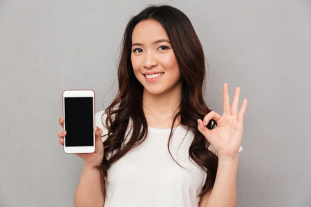 Closeup photo of chinese woman in casual t-shirt demonstrating copyspace screen of modern smartphone and showing ok sign isolated over gray background Stockfoto