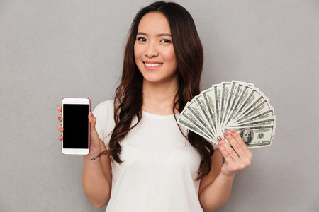 Portrait of asian lucky woman 20s holding fan of money dollar banknotes and demonstrating copyspace screen of cell phone isolated over gray background Standard-Bild
