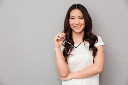 Glückliche asiatische Frau im T-Shirt beißt Brillen und betrachtet die Kamera über grauem Hintergrund