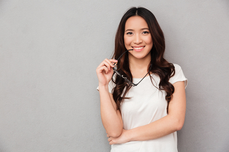 Happy asian woman in t-shirt bites eyeglasses and looking at the camera over grey background