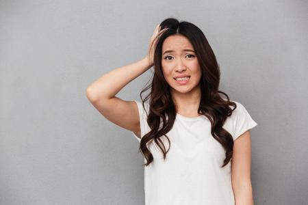 Retrato de mujer asiática 20s con cabello rizado oscuro tocando su cabeza y expresando preocupación aislado sobre fondo gris