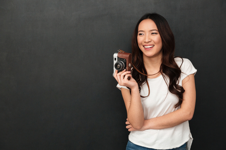 Cheerful asian woman in t-shirt holding retro camera and looking away over black background