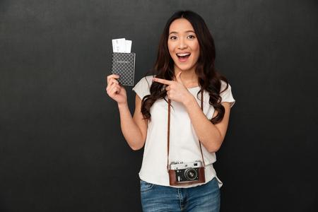 驚くほど興奮したアジアの若い女性観光客の画像は、指差しながらチケットでカメラとパスポートを保持する黒い壁の背景の上に隔離されています