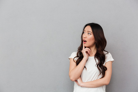 Portrait of chinese surprised woman with dark curly hair posing on camera and looking aside on copyspace with finger on lips isolated over gray background Stock Photo